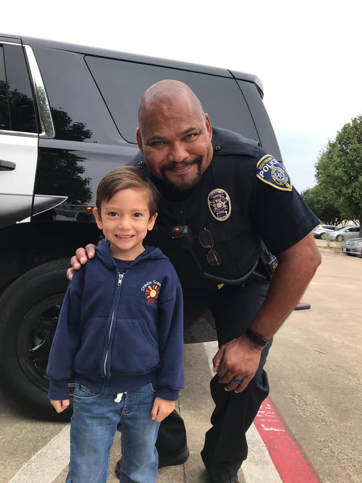 Preschooler with police officer and truck