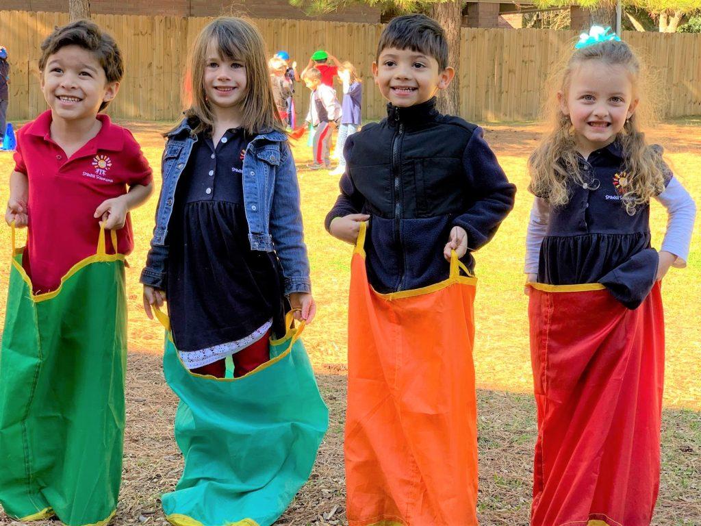 spanish schoolhouse new families, spanish schoolhouse students; preschoolers sack race' happy preschoolers